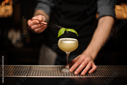 Foto auf Leinwand Alkohol Close-up of the bartender pouring cocktail using forceps