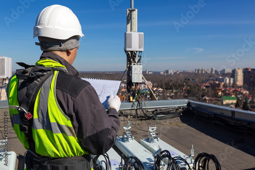 Photo Professional industrial climber in helmet and uniform reads technical documentation and antennas of GSM DCS UMTS LTE bands, outdoor radio units on the roof