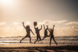 canvas print picture - Group of people jump happy together at the beach during sunset with sky in background and silhouette bodies - summer vacation holiday for friends people have fun in outdoor leisure activity