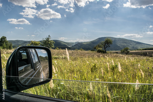 Photo  Suv rear view mirror shot while off roading on a beautiful field.