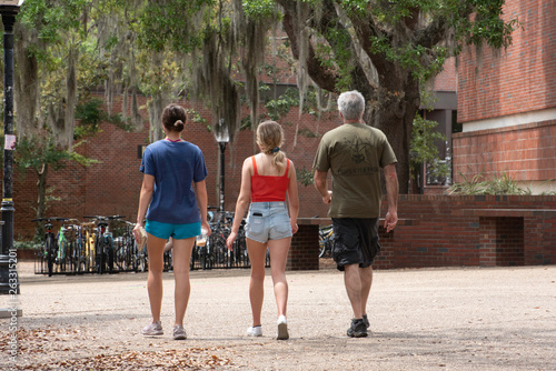 An incoming freshman tours a college campus with her parents. Canvas-taulu