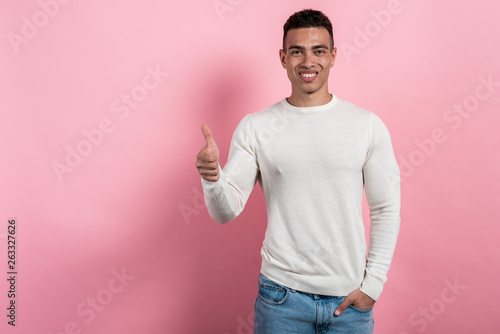 Fényképezés Pretty man on pink studio background shows thumb up