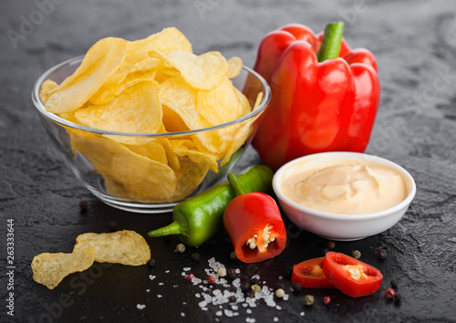Poster Pays d Asie Glass bowl plate with potato crisps chips with onion flavour on black stone table background. Red and green chilli peppers with paprika and hot spicy sauce.