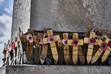 Wooden Crosses With Paper Poppies Fading On A Cenotaph
