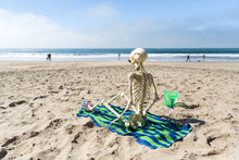 Skeleton Sits On A Beach Towel...