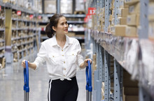 Close Up Shot Of Asian Pretty Customer Searching Products In Store Warehouse. The Girl Pushing The Cart And Find The Goods To Put It In The Cart. Shopping Concept.