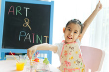 Young Little Asian Girl Painting Plaster Dolls In Painting Class At Home. She Is Raising The Hand And Smile With Happiness. Happy And Fun Education, Creative Activity Concept.