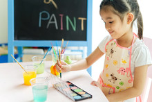 Young Little Asian Girl Painti...