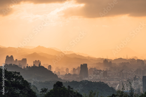 Layers of Taipei cityscape and mountains with sunlight when the sun going down that view from Xiangshan Elephant Mountain in the evening in Taipei, Taiwan.