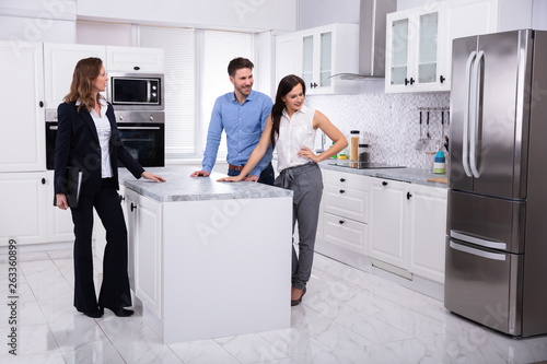 Real Estate Agent Showing Refrigerator In House To A Couple Wallpaper Mural