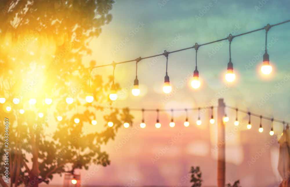 Fototapety, obrazy: blurred bokeh light on sunset with yellow string lights decor in beach restaurant