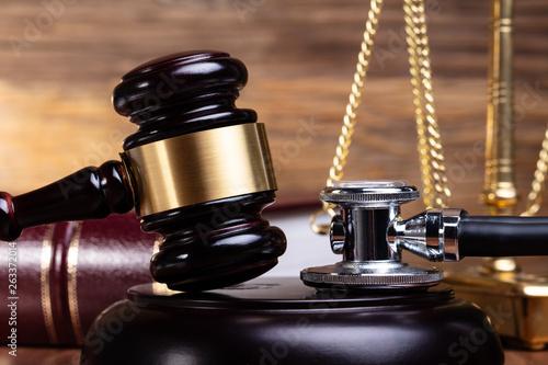 Stethoscope And Gavel On Wooden Desk
