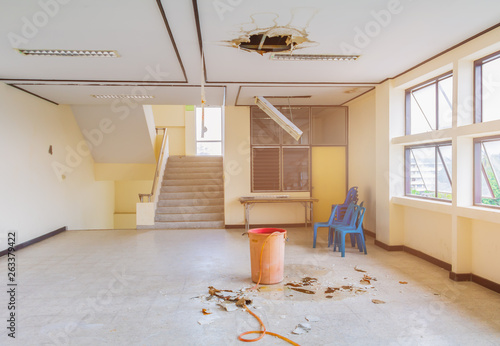 Foto auf Leinwand Wasserfalle water leak drop interior office building in red bucket from gypsum ceiling and flow on terrazzo floor