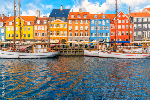 Nyhavn area of popular bar and restaurant at beautiful blue sky, with colorful facades of old houses and old ships in the Old Town of Copenhagen, capital of Denmark Canvas Print