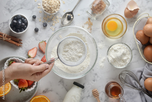 Photo Making pancakes, cake, baking of baker hands pouring or sifting flour in bowl