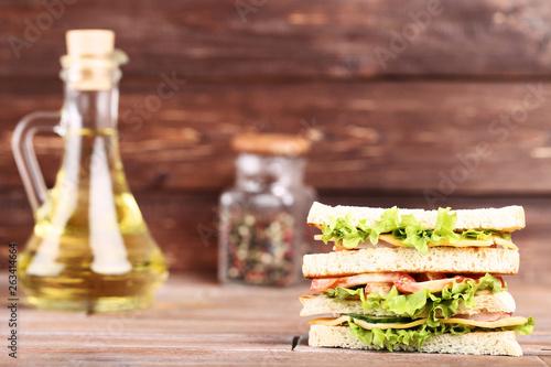 Obraz na plátně Tasty sandwich with oil in bottle on brown wooden background