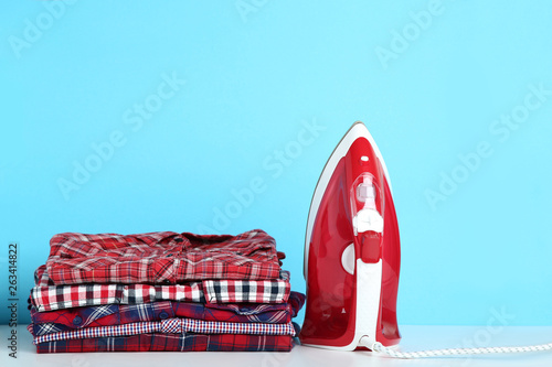 Foto  Stack of folded clothes with electric iron on blue background