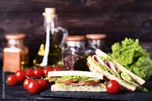Photo  Sandwiches with ham, cheese and vegetables on black wooden table