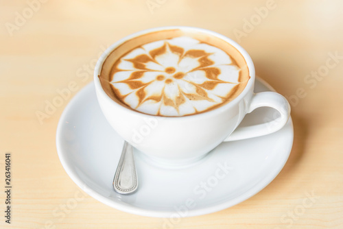 Fotografia hot cappuccino coffee with nice pattern foam on table
