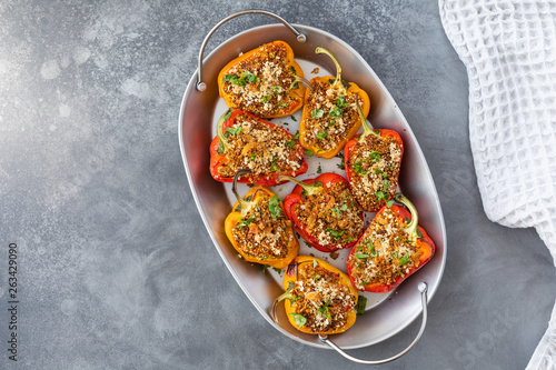Obraz Vegetarian dish with peppers stuffed with quinoa, onion and tomato, sprinkled with walnuts. Top view on gray background - fototapety do salonu