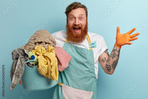 Fotomural  Overjoyed red haired man with foxy thick beard, raises hand, being very happy, w