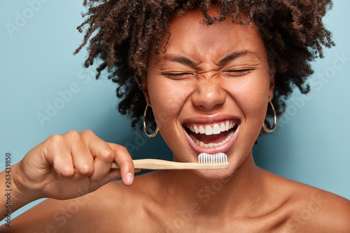 Papiers peints Individuel Cropped shot of cheerful glad dark skinned lady shows white teeth, has overjoyed expression, good mood in morning, prepares for dentist visit, stands with half naked body, isolated on blue wall