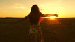 young girl travels in headphones and with smartphone in flight under rays of a warm sunset. Slow motion. Traveler. happy girl listening to music and dancing in the rays of a beautiful sunset in park.