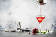 Preparation Classic Alcoholic Cocktail Cosmpolitan With Vodka, Liqueur, Cranberry Juice, Lime, Ice And Orange Zest, Gray Bar Counter Background, Place For Text