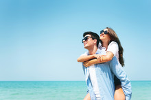 Happy Young Couple Wear Sunglasses Having Fun On Blue Sky And The Beach.