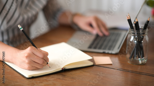 Fotografie, Obraz  Businesswoman writing note while using laptop at table in office