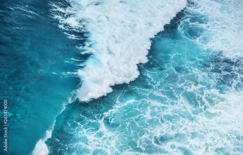 Waves and azure water as a background. View from high rock at the ocean surface. Natural summer seascape. Water background.