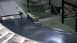 Newspapers flow along an assembly line in a newspaper print factory. UHD 4K s