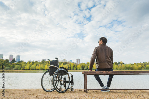 Valokuva  A young man sits on a bench by the lake, next to his wheelchair.