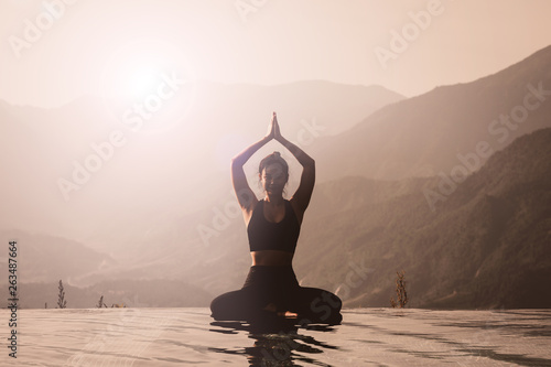 Fotobehang School de yoga Beautiful Asian woman practice yoga Lotus pose on the pool above the Mountain peak in the morning in front of beautiful nature views,Feel so comfortable and relax with yoga in holiday,Warm tone