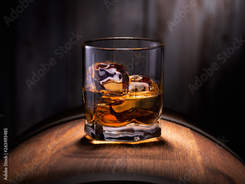 Poster Alcohol Glass of whiskey with ice cubes on the wooden barrel with wooden background