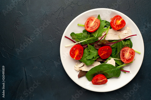 Spoed Fotobehang Voorgerecht Mix fresh leaves of arugula, lettuce, spinach, tomato and chicken fillet for salad, on a white plate on a stone background with copy space for your text