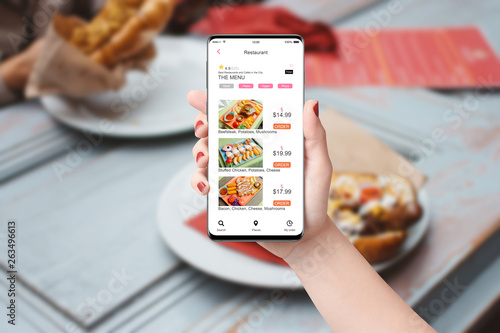 Woman in the restaurant ordering food with app on her phone, blurred table with food in background