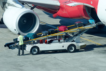 Worker Loads The Luggage In The Plane. Airport Ground Staff.