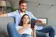 canvas print picture - Young couple watching online content in a smart phone sitting on a sofa at home in the living room.