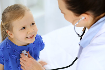 Doctor examining a little girl by stethoscope. Happy smiling child patient at usual medical inspection. Medicine and healthcare concepts