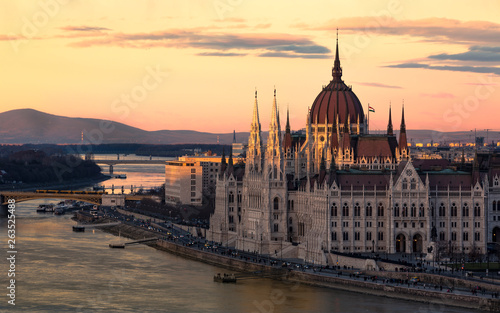 Foto auf Leinwand Budapest Cityscape of Budapest with bright parliament illuminated by last sunshine before sundown and Danube river with bridge. Pink and purple colors of sky reflecting in water during sunset.