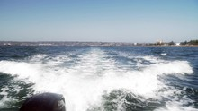 4k. Looking Back From Motor Boat. Motor Creates Waves On The Ocean Surface.