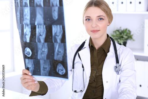 Fotografía Doctor woman examining x-ray picture near window in hospital