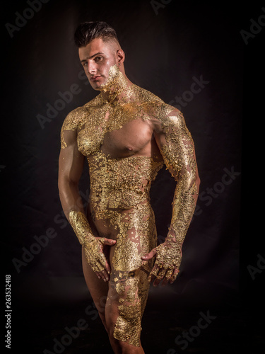 Muscular naked man covered with golden ing chin and looking down sensually on black background