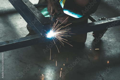 Worker welding steel frame with MIG technology