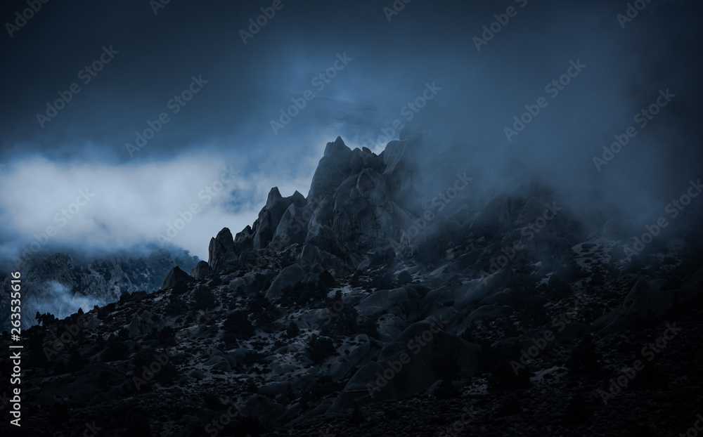 Fototapeta Rocky mountain peaks surrounded by misty fog in the Sierra Nevada mountains near North Lake in Eastern California. The ominous foggy weather creats an emotional feel to the mist filled rugged scene