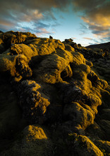 Soft Moss Covered Rocks Near The Coast Of Iceland In Mid Summer. The Lush Green Texture Covers The Hard, Rugged Rock Beneath It. The Sun Rim Lights Up The Emerald Texture And Colors The Skies Clouds