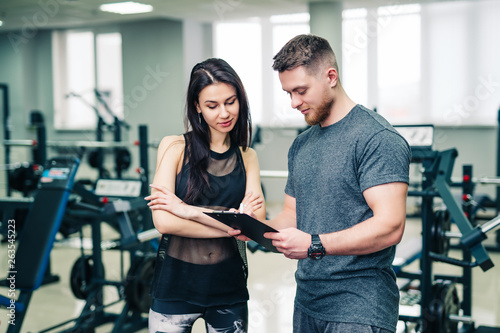 Muscular coach shows the woman's sport results on the background of gym. Personal trainer and young female talking about the progress inside the sports club.