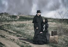 Outdoors Portrait Of A Victorian Lady In Black Sitting On The Road With Her Luggage And Gentleman Standing Nearby.