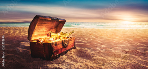 Fotomural  treasure chest at the beach by sunset